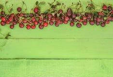 Saftige frische Kirschen auf einem hellen hölzernen Hintergrund Stockbilder