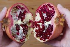 Saftige Hälften des Granatapfels in den Händen Stockbild