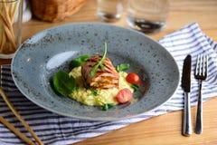 Saftige Hühnerrolle mit Risotto, Kirschtomaten und dem Grün auf einer Platte diente für ein Abendessen in einem Restaurant Geschm Lizenzfreie Stockbilder
