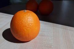 Saftige Orange beleuchtete auf dem Tisch durch eine helle Morgensonne stockfotos