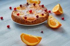 Saftige orange Scheibe auf dem Vordergrundabschluß oben Selbst gemachter orange Kuchen mit frischen roten Moosbeeren, Orangen auf Lizenzfreie Stockbilder
