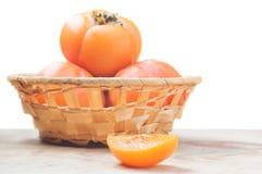 Saftige Persimonescheibe mit unscharfen Früchten herein Stockfotografie