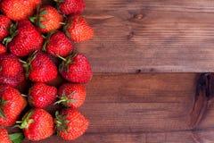 Saftige reife Erdbeere auf Holz Stockbilder