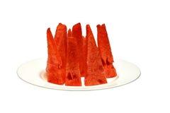 Saftige Scheiben des Wassermelonenfleisches stehend auf einer weißen Platte Lizenzfreie Stockbilder