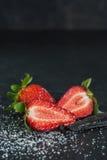 Saftiger Erdbeere-whith Zucker und Vanille auf dem schwarzen backgroun Stockfoto