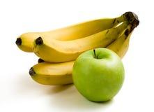 Saftiger grüner Apfel und reife gelbe Bananen Stockfotografie