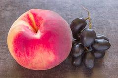 Saftiger Pfirsich auf einem schwarzen Hintergrund Bündel schwarze Trauben Stockfoto