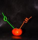 Saftiger reifer Tomatensaft mit einem Stroh auf einem schwarzen Hintergrund Stockfoto