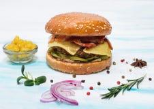 Saftiger Rindfleischburger mit Käse, Gurken, Speck auf einem weißen Hintergrund stockfotos