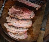 Saftiges Stück von Schweinefleisch, von Pfeffer, von noh und von Gabel auf einem hölzernen Hintergrund Lizenzfreie Stockbilder
