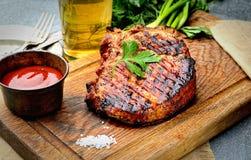 Saftiges Steak auf dem Brett, Bier, Ketschup, Petersilie, Zwiebel und andere Grüns, Messer und Gabel Stockbild