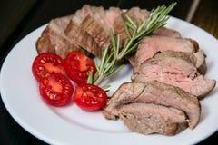 Saftiges Steak auf der Platte mit Tomaten Lizenzfreies Stockbild