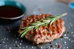 Saftiges Steak auf einer Platte mit Soßenumhüllung für ein Abendessen in einer Steakhouse Makrolebensmittelhintergrund Stockbilder