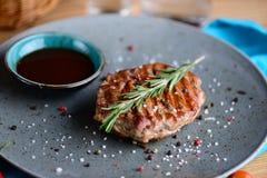 Saftiges Steak auf einer Platte mit Soßenumhüllung für ein Abendessen in einer Steakhouse Makrolebensmittelhintergrund Lizenzfreie Stockfotografie