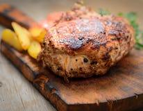 Saftiges Steak mit Kartoffeln, Tomaten und Kräutern auf einem Schneidebrett Stockfotos