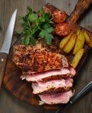 Saftiges Steak mit Kartoffeln, Tomaten und Kräutern auf einem Schneidebrett Lizenzfreie Stockfotos