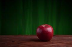 Saftigt äpple på ett wood skrivbord Arkivfoto