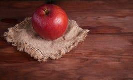 Saftigt äpple på ett wood skrivbord Arkivfoton