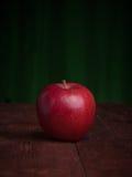 Saftigt äpple på ett wood skrivbord Royaltyfria Foton