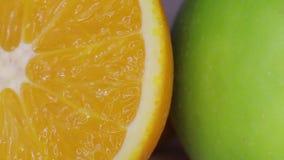 Saftigt apelsin- och gräsplanäpple arkivfilmer
