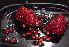 Saftigt frö av granatäpplet i egen fruktsaft Slut upp mot en mörk bakgrund arkivbild