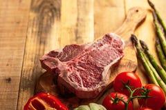 Saftigt nytt stycke av marmorerad nötköttbiff med grönsaker för att grilla Kulinarisk bakgrund, receptbok, läcker mat, biff arkivbild