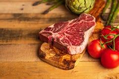 Saftigt nytt stycke av marmorerad nötköttbiff med grönsaker för att grilla Kulinarisk bakgrund, receptbok, läcker mat, biff fotografering för bildbyråer