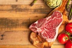 Saftigt nytt stycke av marmorerad nötköttbiff med grönsaker för att grilla Kulinarisk bakgrund, receptbok, läcker mat, biff arkivfoto