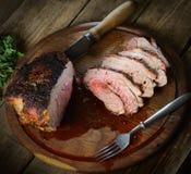 Saftigt stycke av griskött, peppar, noh och gaffeln på en träbakgrund royaltyfri fotografi