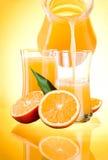 Saftpitcher, Orangen mit Blättern auf gelbem backgr Lizenzfreies Stockbild
