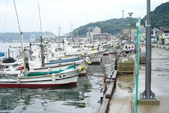 Saga, Japan:September 1, 2016 - Landscape with group of fishing boat parking at the port with cityscape in background. Traditional royalty free stock photo
