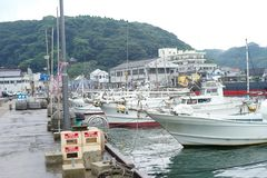 Saga, Japan:September 1, 2016 - Landscape with group of fishing boat parking at the port with cityscape in background. Traditional stock photography