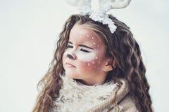 Sagaflicka Flickan för ståenden i en hjort klär lite med en målad framsida i vinterskogen Fotografering för Bildbyråer
