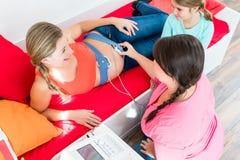 Sage-femme de observation de jeune fille attachant CTG au ventre enceinte de m photographie stock libre de droits