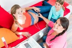 Sage-femme de observation de jeune fille attachant CTG au ventre enceinte photo libre de droits