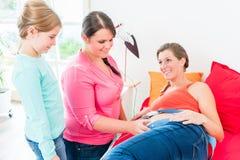 Sage-femme de observation de jeune fille attachant CTG au ventre enceinte de m image libre de droits