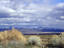 Sage, Mountains and Clouds. Sagebrush growing along a livestock fence, with snow-capped mountains in the background and dramatic clouds hovering overhead. Taken Royalty Free Stock Images