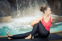 Sage Twist. Marichyasana. Woman practicing yoga near waterfall. Sage Twist. Marichyasana Stock Photography