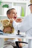 Sagen Sie aaah - kleinen Jungen am Doktor Stockbilder