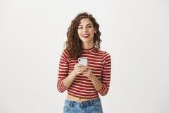 Sagen Sie mir Ihrer Telefonnummer Atelieraufnahme der glücklichen reizend kaukasischen Frau mit dem gelockten Haar und rotem Lipp lizenzfreies stockfoto