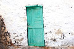 Sagging blue door old white wall front, Canary islands, Spain royalty free stock photos