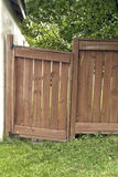 Sagging Gate. A sagging wooden gate over a grass area with trees behind Stock Photos