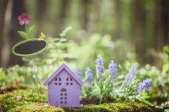 Sagolikt leksakhus, färgerna av lavendel med ett tecken för inskrift, mot bakgrunden av en felik skog royaltyfri foto