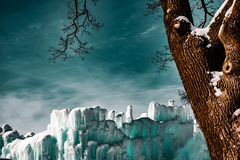 Sagolikt vinterlandskap med det isväggen och trädet arkivbild