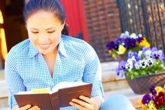 Sagrada Biblia bonita de la lectura de la mujer de la raza mixta Imagen de archivo libre de regalías