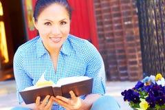 Sagrada Biblia bonita de la lectura de la mujer de la raza mixta Foto de archivo