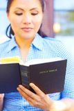 Sagrada Biblia bonita de la lectura de la mujer de la raza mixta Fotos de archivo libres de regalías