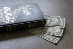 Sagrada Biblia cirílica con los dólares del dinero Imagenes de archivo