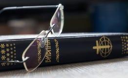 Sagrada Biblia cirílica con los vidrios Foto de archivo libre de regalías