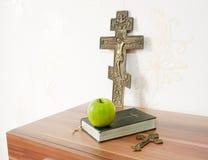 Sagrada Biblia con la manzana verde y dos cruces Imágenes de archivo libres de regalías